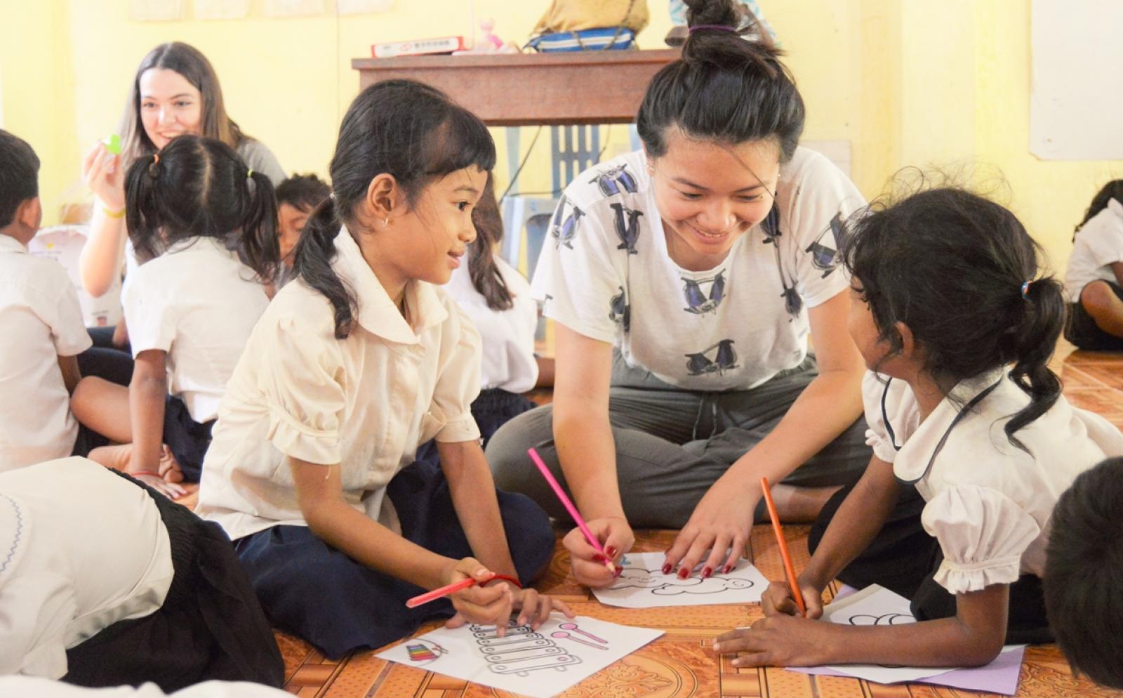カンボジアで図画工作に取り組む子供たちとチャイルドケアボランティア